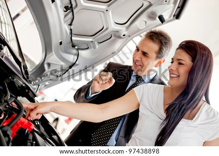 Woman at the dealer looking at a car engine