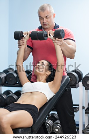 Woman at the health club with her personal trainer, learning the correct form with barbell