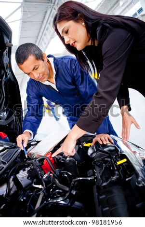 Woman at the mechanic having problems with her car