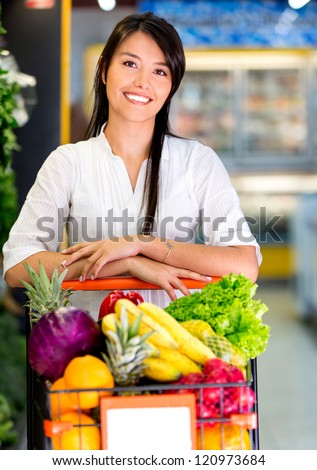Woman at the supermarket with a shopping cart full of groceries