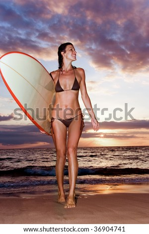 woman at tropic sunset with surfboard in maui, hawaii
