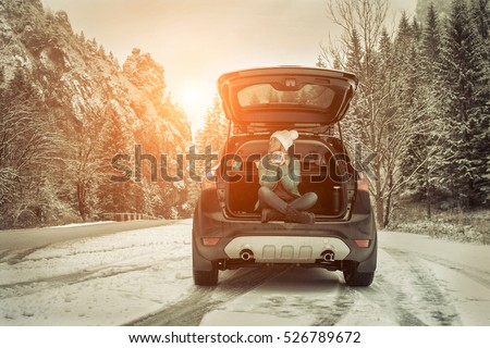 Woman at winter time. Yoyng female with hot tea in her hands sitting in black car at snowly winter day.