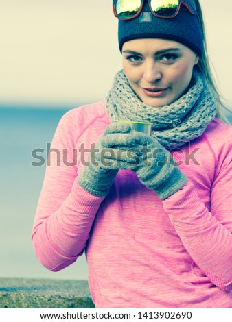 Woman athlete fit girl wearing warm sporty clothes outdoor in cold weather drinking hot tea from vacuum flask thermos, warming up. Sports, activities, hiking in winter or autumn time #1413902690