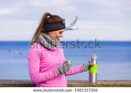 Woman athlete fit girl wearing warm sporty clothes outdoor in cold weather drinking hot tea from vacuum flask thermos, warming up. Sports, activities, hiking in winter or autumn time #1481337206