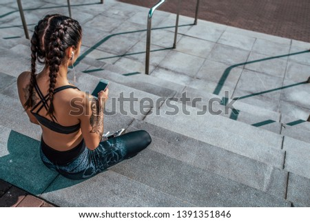 Woman athlete in tattoos, in summer city, resting after workout fitness, workout. Sportswear leggings top. Headphones smartphone. Online application social networks. Listening to music. Free space.