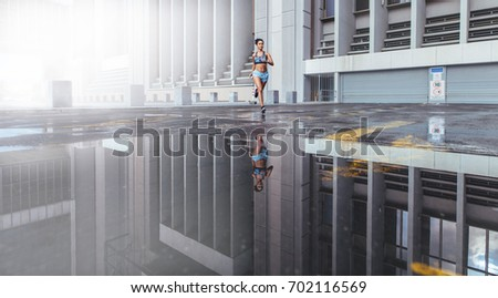 Woman athlete running outdoors in the morning. Reflection of woman runner on water surface in front of a large city building.