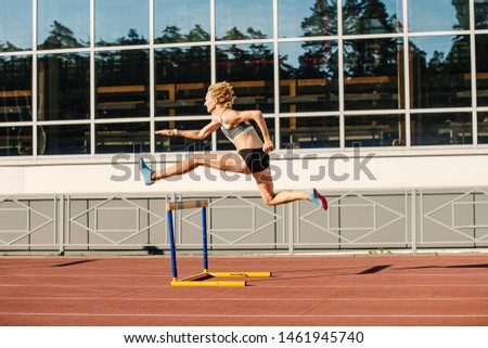 woman athlete runnner running hurdles in summer athletics competition