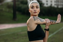Woman athlete with tattoo on her arm doing stretching exercises in a ground. Portrait of a woman in fitness clothes doing warm up exercises.