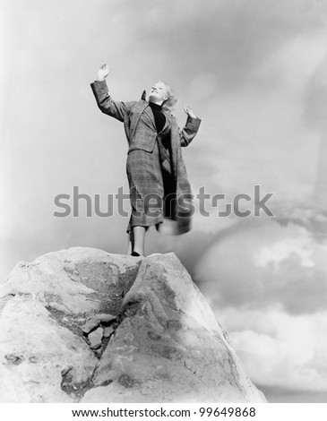 woman atop rock on windy day