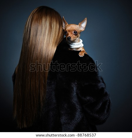 Woman back in a fur coat with the small dog.
