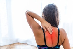 Woman back sport red area pain. Body pain. Young woman with pain in her back. Neck pain during training.  Woman with sport injury rubbing and touching upper back muscles inside after exercise workout