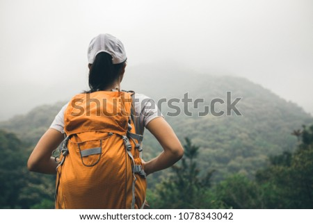 Woman backpacker enjoying the view on morning mountain valley #1078343042