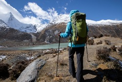 Woman backpacker hiking in winter high altitude mountains