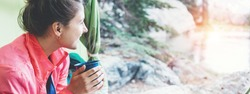 Woman backpacker sitting inside the tent and looking at fresh and beautiful nature. Drinking hot tea in the morning. Wide screen panoramic