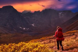 Woman Backpacking on Scenic Hiking Trail to Lake surrounded by Mountains during Fall in Canadian Nature. Colorful Dramatic Sunset Sky Artistic Render. Tombstone Territorial Park, Yukon, Canada.