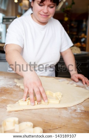 Woman baker making Christmas biscuits cutting out the shapes from a rolled out portion of pastry