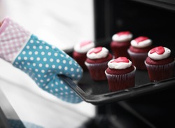 Woman baking cupcakes in the oven