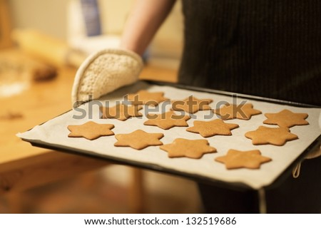 Woman baking ginger bread stars for Christmas. Natural Colors. Real life