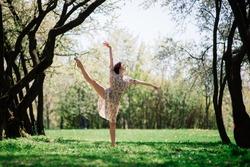 Woman ballerina in blooming garden. pink. Portrait of dancing female outdoor.