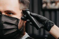 Woman barber cutting hair to a bearded man in face mask. Quarantine haircut concept.