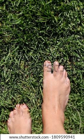 Woman bare feet on the grass. Selective focus