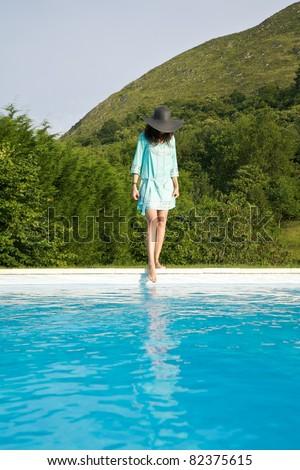 woman barefoot at swimming pool border in Asturias Spain - stock photo