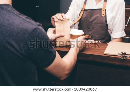 Woman barista giving coffee cup to customer at cafe #1009420867