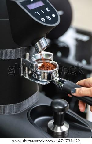Woman barista grind coffblackdayee beans into the portafilter