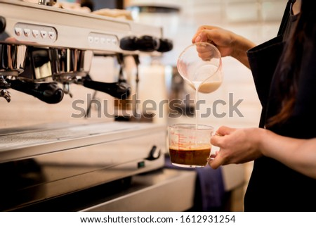 Woman barista pours milk into coffee making iced coffee.
