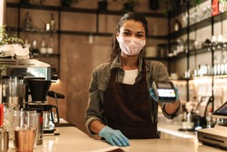 Woman barista wearing medical face mask holding cashless terminal to pay for order at the counter