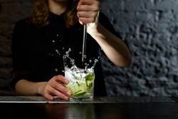 Woman barman making alcoholic cocktail and squeezing juice from fresh lime in glass which splashing out