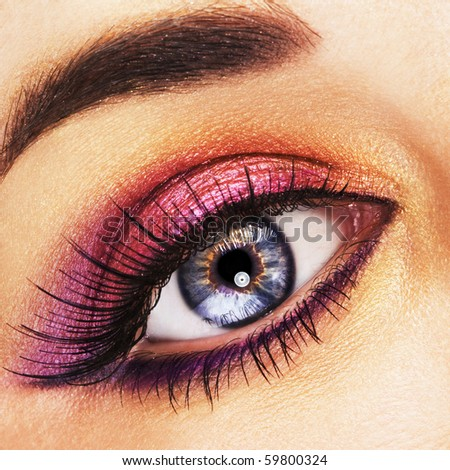 Woman beautiful eye with golden and pink makeup