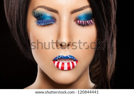 Woman beautiful face with perfect makeup on black background. on the lips and eyes painted an American flag
