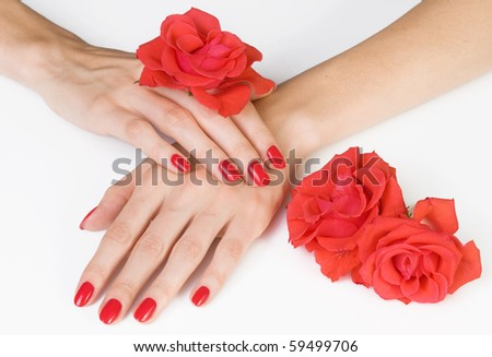 Woman beautiful hands with red manicure and scarlet roses