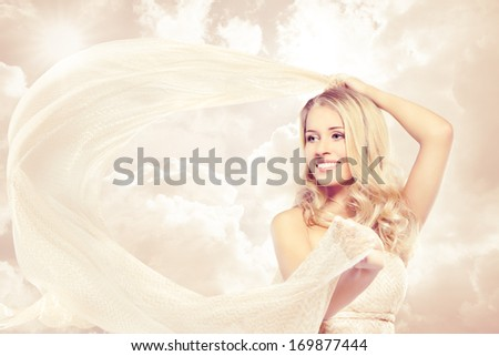 Woman beautiful happy blonde carefree smiling with flying fabric over sky background