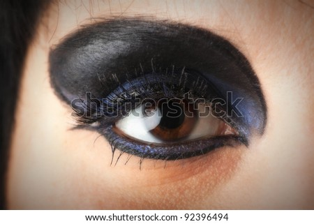 woman Beautiful shape of female eye with black blue cosmetic make-up Professional make up