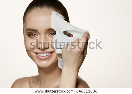 Woman Beauty Face. Closeup Of Smiling Young Female With Fresh Natural Makeup Removing Textile Sheet Mask From Facial Skin. Portrait Of Attractive Happy Girl With White Cosmetic Mask. High Resolution #646511806
