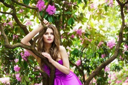 Woman Beauty Face Pink Dress Outdoors. Fashion Model Girl inPurple Gown Flower Blooming Spring Garden. Sunshine Floral Summer Background