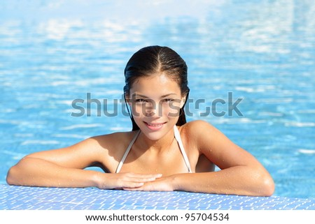 Woman beauty in pool on vacation holiday resort. Gorgeous natural beautiful woman in swimming pool smiling happy. Multiracial young female  model in bikini outdoor. Mixed race Asian Chinese Caucasian.