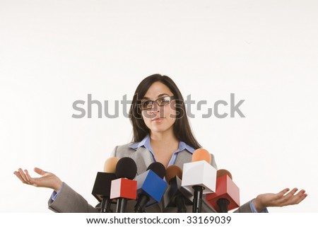 woman behind a bank of microphones