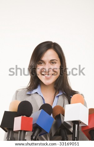 woman behind bank of microphones