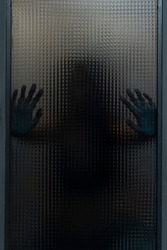 Woman behind textured glass. Hands resting on the glass. Dramatic theme photography. Terror, confinement, horror, despair, violence, claustrophobia.