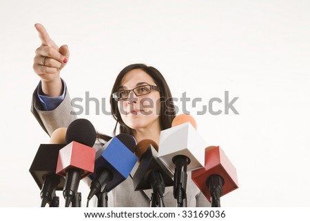 woman behing a bank of microphones pointing