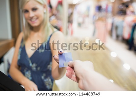 Woman being handed credit card in clothing store