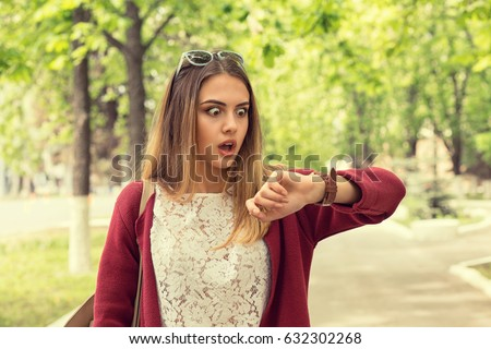 Woman being late to a rendez-vous. Closeup portrait headshot view stressed young attractive beautiful businesswoman checking the time outdoor isolated park cityscape outdoor background. Mixt race girl