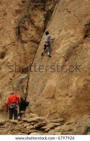 Woman belaying a climber on rock face,Smith Rock State Park, Central Oregon