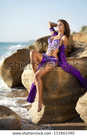 woman belly dancer on rock beach. dancing beautiful slim girl. sexy arabian turkish oriental professional artist in carnival blue costume and diamond jewelry outdoor. exotic bellydance star. Series