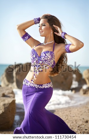 woman belly dancer on sea beach. dancing beautiful slim girl. sexy arabian turkish oriental professional artist in carnival violet costume and diamond jewelry outdoor. exotic bellydance star. Series