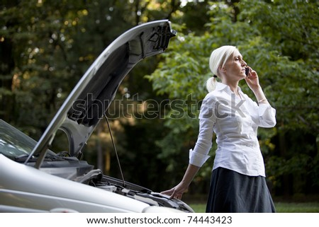 Woman besides her broken car talking on the cell phone