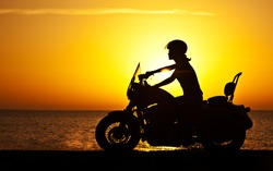 Woman biker over sunset, female riding motorcycle, motorbike driver traveling, girl racing on the beach road, freedom lifestyle